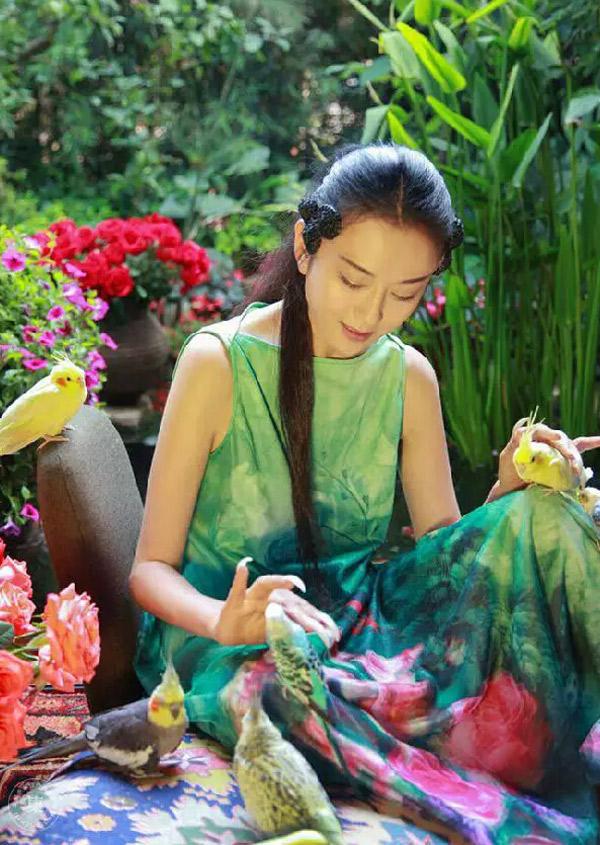 富安娜艺术家纺代言人杨丽萍又出大片啦!近日杨丽萍在云南昆明家中的后花园里看书,她身着红绿搭配的飘逸长裙,色彩浓郁,风格独特,与富安娜的风格很相符!<br /> 杨丽萍簇拥在色彩浓郁的鲜花里,像极了从森林中走出的精灵,充满了大自然的灵韵,清新而脱俗。美得哭!